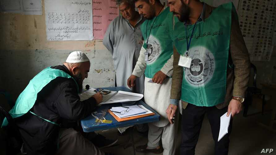 This photo taken on April 14, 2018, shows Afghan employees of the Independent Election Commission registering a resident at a voter registration center for the upcoming parliamentary and district council elections in Kabul.