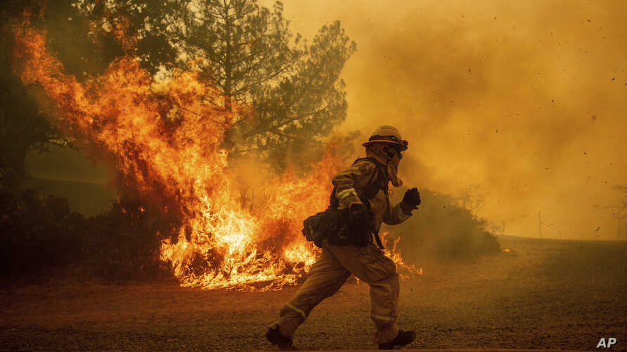 A firefighter runs while trying to save a home as a wildfire tears through Lakeport, Calif., July 31, 2018.