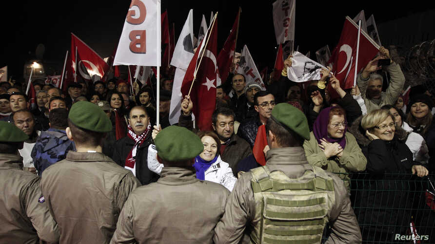 Pro-secular demonstrators wait for the release of former army chief Ilker Basbug outside the Silivri prison complex near Istanbul, Turkey, March 7, 2014.
