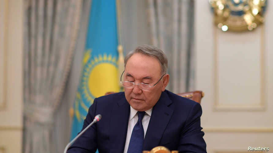 Kazakhstan's President Nursultan Nazarbayev writes during a televised address to announce his resignation, in Astana, Kazakhstan, March 19, 2019.