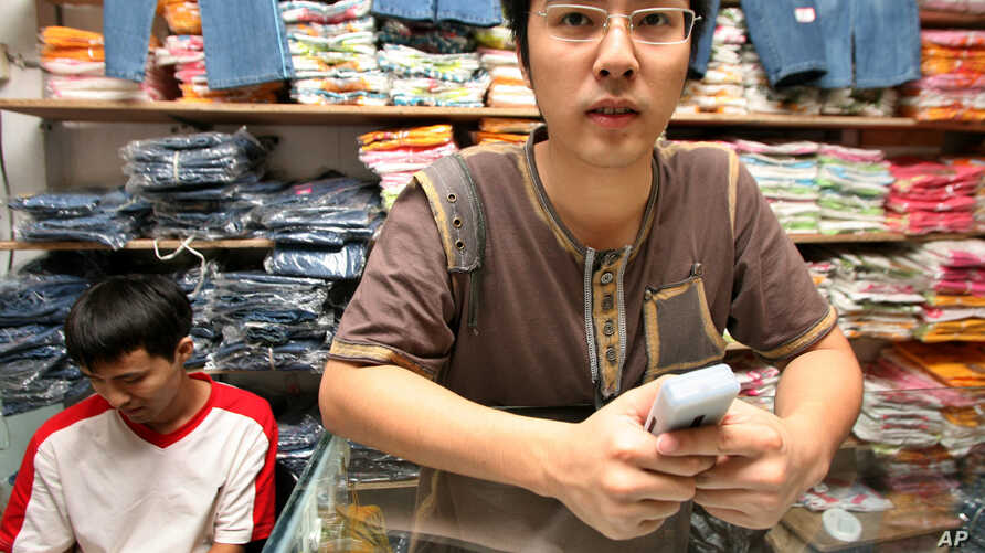 An unidentified Chinese trader stands near clothing materials for sale inside his shop at the China town trading building in Lagos, Nigeria, August 1, 2006.