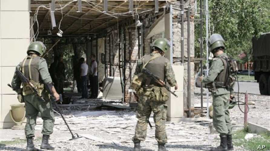 Security personnel stand guard at scene of suicide bombings in central Grozny, Chechnya, Aug. 31, 2011