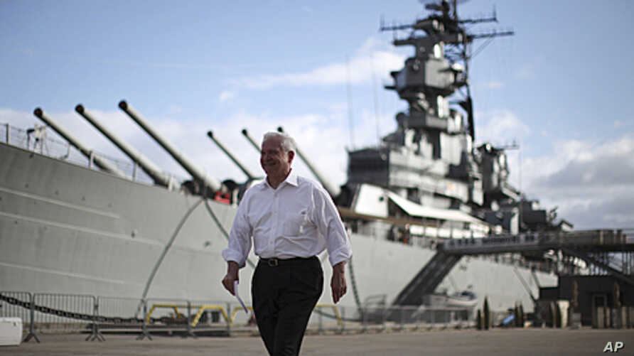 U.S. Secretary of Defense Robert Gates walks alongside the USS Missouri battleship during his visit to Hawaii, May 31, 2011