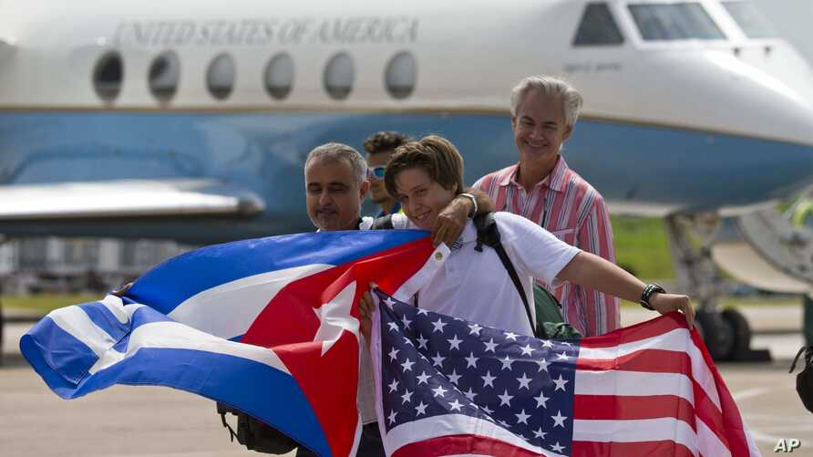Passengers of JetBlue flight 387 holding a United States, and Cuban national flags, pose for photos in front of the plane transporting U.S. Transportation Secretary Anthony Foxx, at the airport in Santa Clara, Cuba,  Aug. 31, 2016