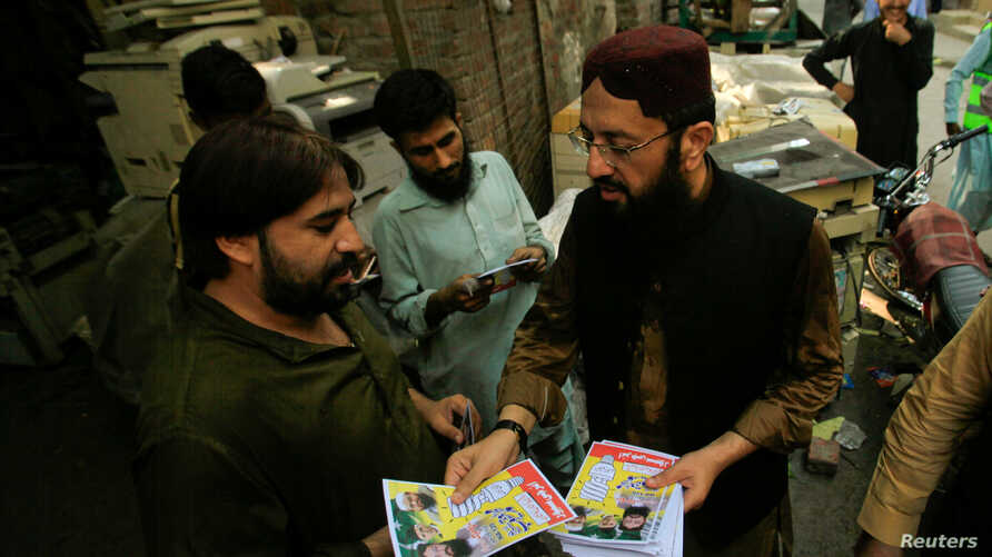 FILE - Mohammad Yaqoob Sheikh, right, nominated candidate of the Milli Muslim League, distributes handbills to residents during an election campaign for the National Assembly NA-120 constituency in Lahore, Pakistan, Sept. 10, 2017.