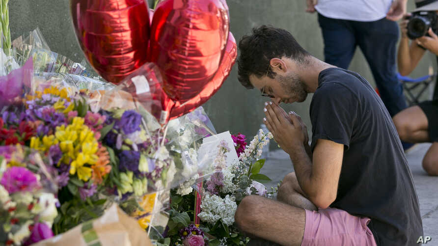 Paolo Singer, 27, a Silver Lake resident, prays at a makeshift memorial of flowers, candles and notes on the sidewalk outside the Silver Lake Trader Joe's store in Los Angeles, July 23, 2018. Trader Joe's employee Melyda Corado was shot and killed at
