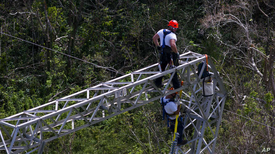 FILE - Whitefish Energy Holdings workers restore power lines damaged by Hurricane Maria in Barceloneta, Puerto Rico, Oct. 15, 2017.