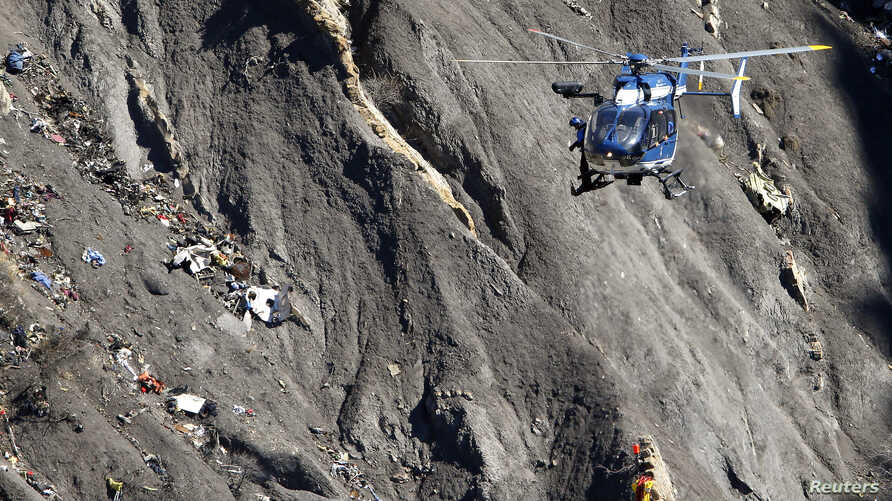A French Gendarmerie rescue helicopter flies over the debris of the Airbus A320 at the site of the crash, near Seyne-les-Alpes, French Alps, March 27, 2015.