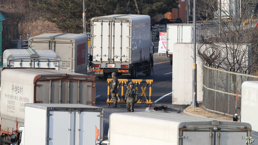South Korean cargo trucks head to the North Korean city of Kaesong as South Korean Army soldiers stand guard at the customs, immigration and quarantine office near the border village of Panmunjom in Paju, South Korea, Feb. 11, 2016.
