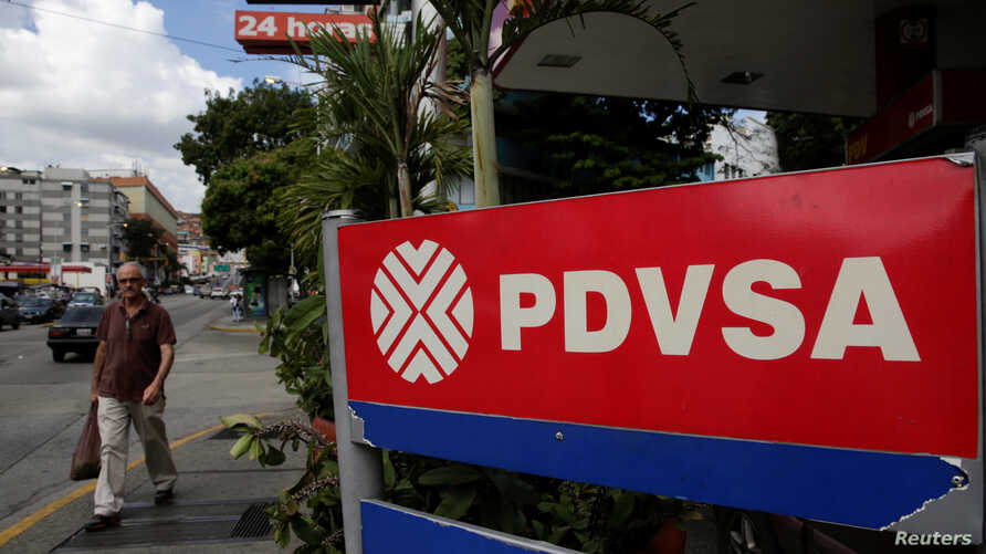 FILE - A man walks past the corporate logo of the state oil company PDVSA at a gas station in Caracas, Venezuela, Dec. 1, 2017.