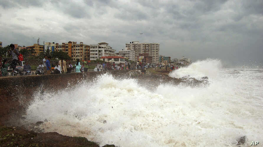 Indian people watch high tide waves as they stand at the Bay of Bengal coast in Vishakhapatnam, India, Oct. 12, 2013. Hundreds of thousands of people living along India's eastern coastline were taking shelter Saturday from a massive, powerful cyclone