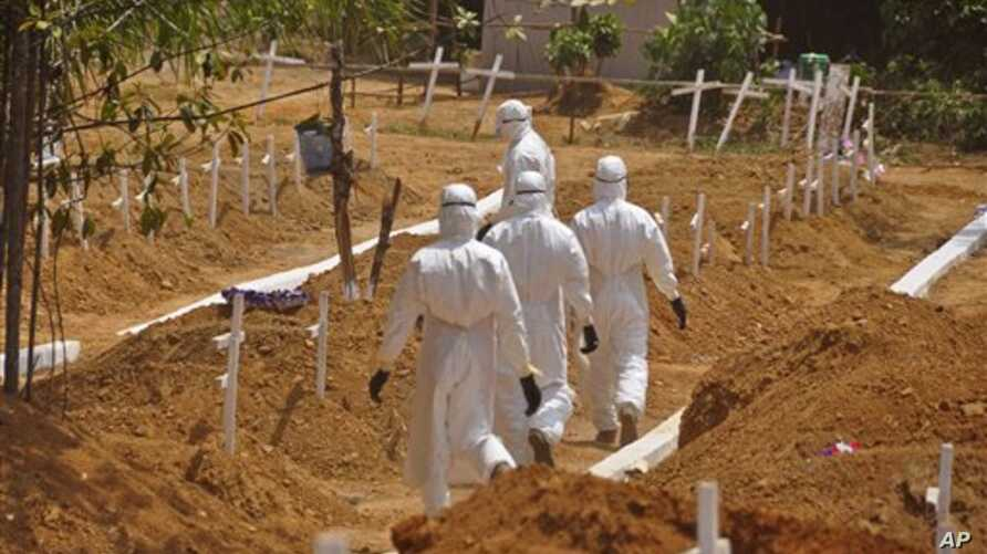 Health workers walk inside a new graveyard as they move bury people suspected of dying from the Ebola virus on the outskirts of Monrovia, Liberia, Wednesday, March 11, 2015. Liberians held a church service Wednesday for families who lost members to E