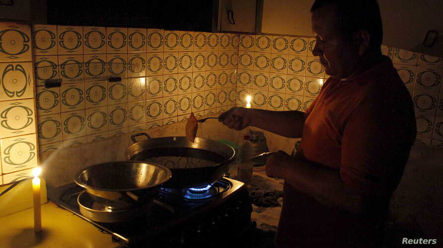 A man cooks near lit candles at his home during a power cut in San Cristobal, in the state of Tachira, Venezuela, April 25, 2016