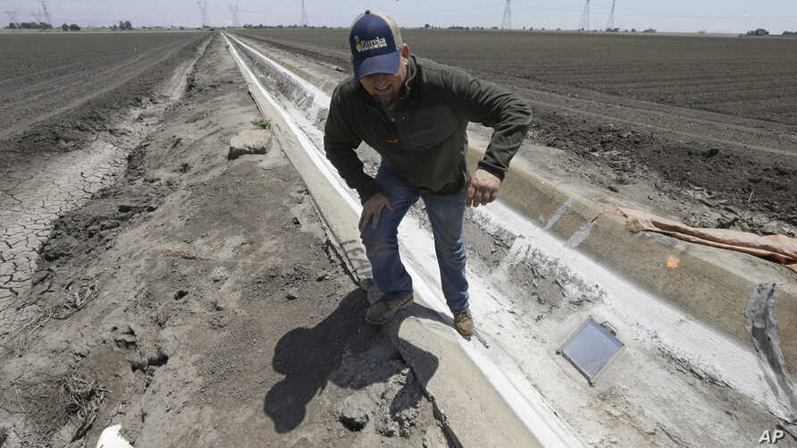 FILE - Farmer Gino Celli climbs out of a irrigation canal that is covered in dried salt on a field he farms near Stockton, Calif., May 18, 2015.