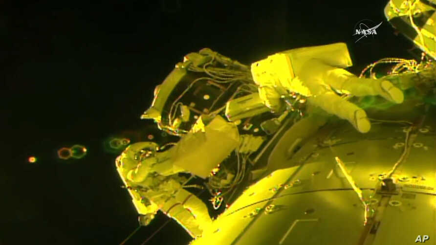 In this image made from video provided by NASA, U.S. astronauts Shane Kimbrough, left, and Peggy Whitson, install a shield on a relocated docking port outside of the International Space Station, March 30, 2017.