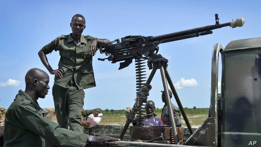 FILE - Government soldiers stand guard by their vehicle on the front lines in the town of Kuek, northern Upper Nile state, South Sudan.