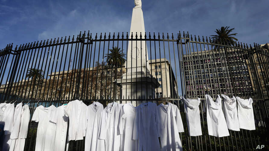FILE - White medical coats hanging from the iron gate that surrounds the national monument May Pyramid, as a symbolic act against efforts to legalize abortion, in Buenos Aires, Argentina, July 15, 2018.