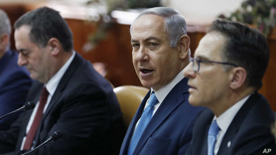 Israeli Prime Minister Benjamin Netanyahu, center, sits next to Cabinet Secretary Tzachi Braverman, right, and Israeli Intelligence and Transportation Minister Israel Katz, at the start of the weekly Cabinet meeting in Jerusalem, Feb. 11, 2018.