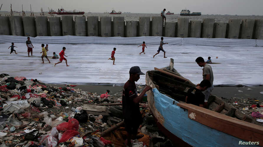 FILE - Fishermen repair their wooden boat as children play soccer near a new construction of a concrete sea wall in Cilincing district of Jakarta, Indonesia, Aug. 22, 2017.