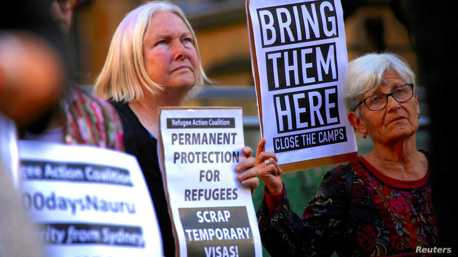FILE - Refugee advocates hold placards and banners during a protest in central Sydney, Australia, Oct. 5, 2016, calling for the closure of the Australian detention centres in Nauru and Manus Island.