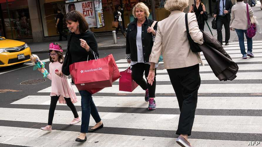 FILE - People carrying shopping bags walk along Fifth Avenue, Sept. 27, 2016 in New York City.