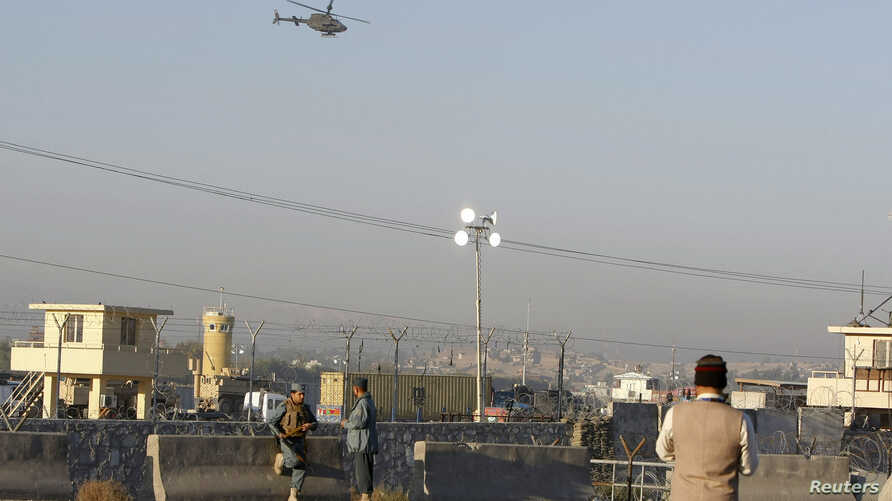 Afghan security forces keep watch as a NATO helicopter flies over at the site of an attack in Jalalabad December 2, 2012. Suicide attackers detonated bombs and fired rockets outside a major U.S. base in Afghanistan on Sunday, killing five people in a