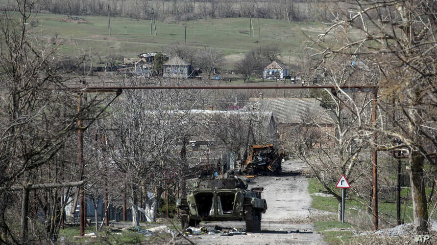 A damaged armed vehicle of Pro-Russian rebels stands between the positions of Pro-Russian rebels and Ukrainian army in Shyrokyne village, eastern Ukraine, April 10, 2015.