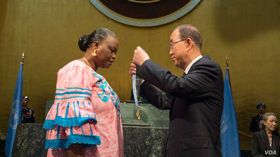 """U.N. Secretary-General Ban Ki-moon presents the """"Captain Mbaye Diagne Medal for Exceptional Courage"""" to Ms. Yacin Mar Diop, widow of Captain Diagne. (UN Photo/Eskinder Debebe)"""