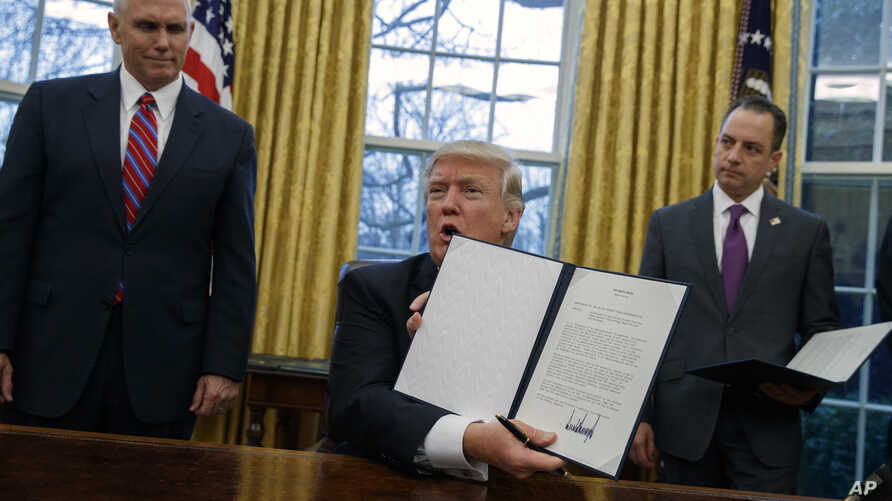 Vice President Mike Pence, left, and White House Chief of Staff Reince Priebus watch as President Donald Trump shows off an executive order to withdraw the U.S. from the 12-nation Trans-Pacific Partnership trade pact agreed to under the Obama adminis