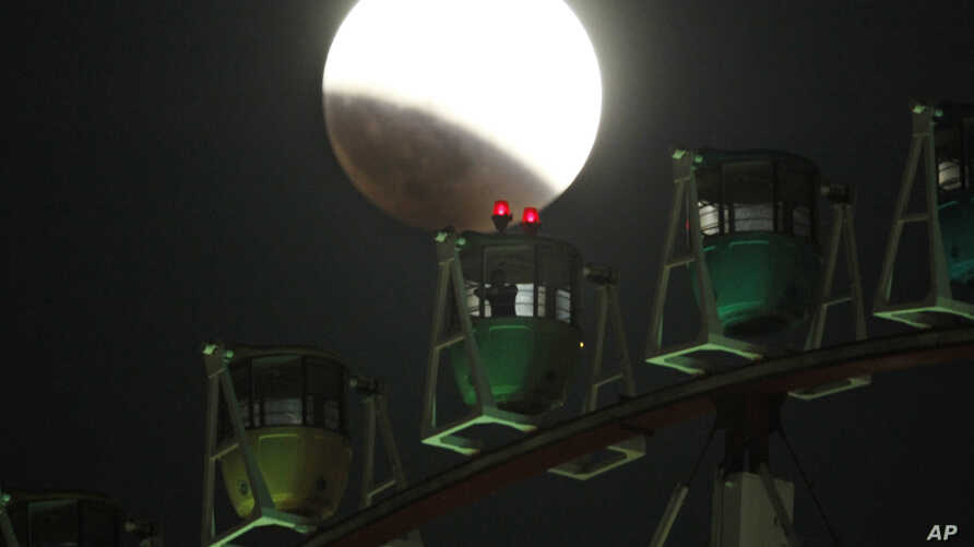The Earth's shadow renders the moon as a person in Ferris wheel observes it during a total lunar eclipse in Tokyo, Wednesday, Oct. 8, 2014. (AP Photo/Koji Sasahara)