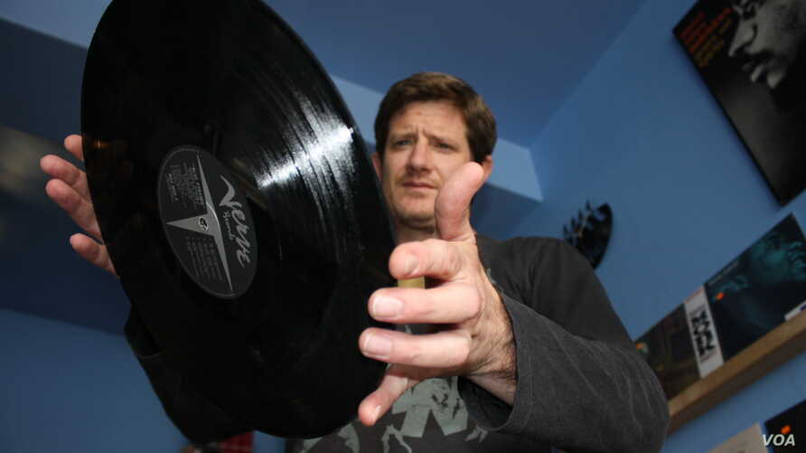 Kevin Stuart about to put another vinyl record on the turntable inside his Record Mad store in Johannesburg. (Darren Taylor for VOA News)