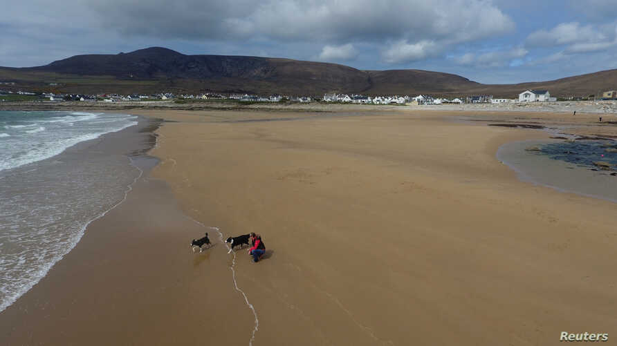 A woman walks her dogs along Dooagh beach after a storm returned sand to it, 30 years after another storm had stripped all the sand off the beach, on Achill island, County Mayo, Ireland, May 5, 2017. (Sean Molloy/Achill Tourism via Reuters)