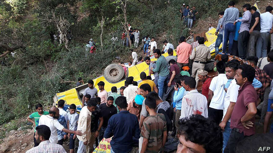 Indian people helping to rescue injured after a private school bus falls into a deep gorge in Nurpur, Kangra district, on April 9, 2018.