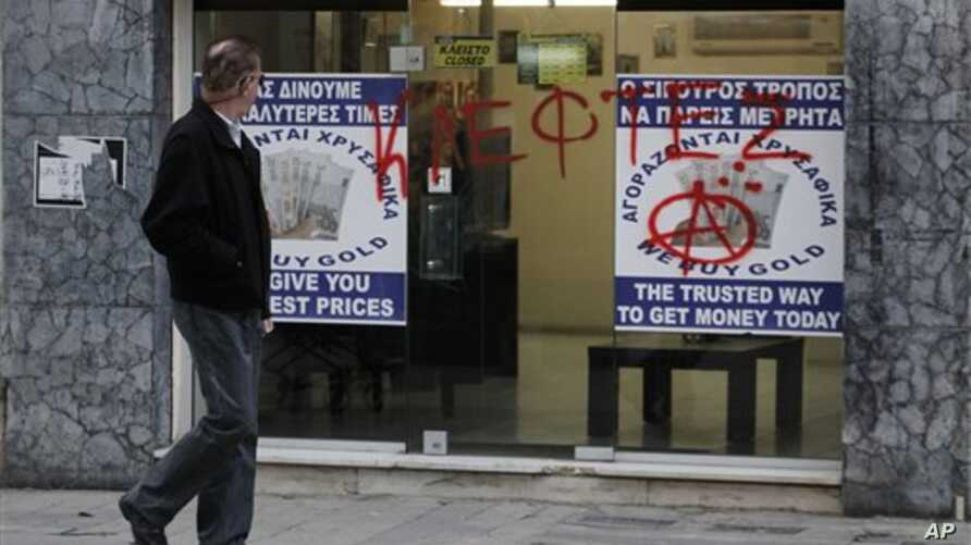 """Man passes entrance of a store that buys gold vandalized with Greek word """"thievess,"""" Nicosia, Cyprus, March 25, 2013."""