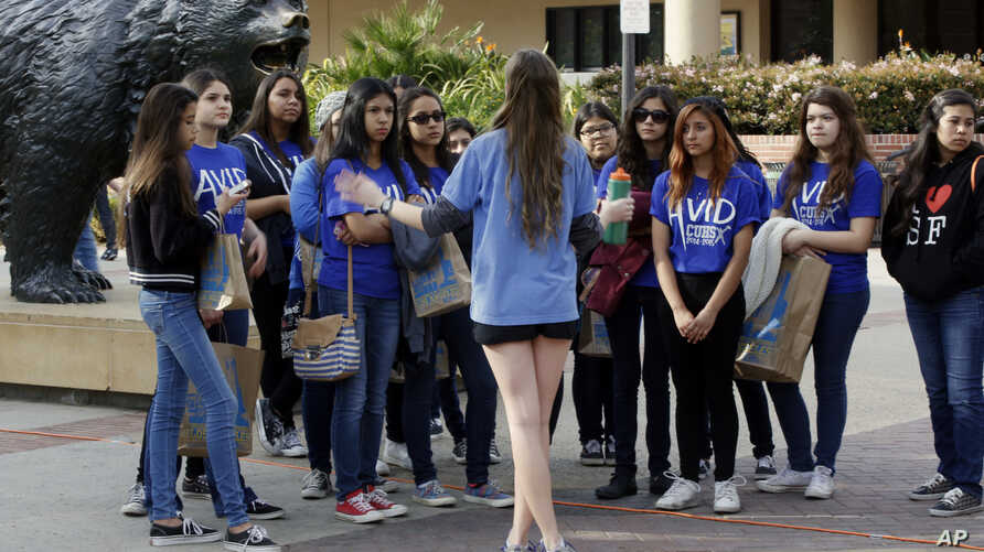 FILE - In this Feb. 26, 2015, file photo, UCLA campus tour guide Samantha St. Germain, center, a bioengineering student, leads prospective college-bound high school seniors on a campus tour in Los Angeles.