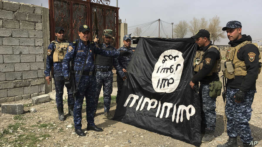 Iraq's federal police forces celebrate as they hold a flag of the Islamic State group they captured after regaining control of Gawsaq neighborhood in the western side of Mosul, Iraq, Feb. 27. 2017.