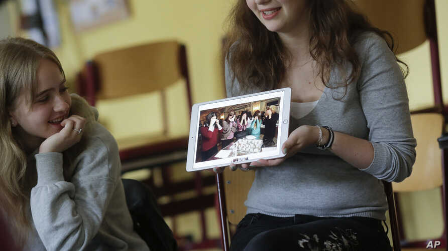 Jewish teenager Sophie Steiert, right, shows a picture of Jewish daily life on a tablet computer as Laura Schulmann looks on during a lesson as part of a project of religions at the Bohnstedt Gymnasium high school in Luckau, Germany, June 25, 2018.