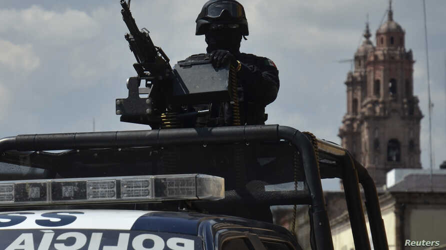 A Federal police patrol mans a weapon atop a vehicle in Morelia, in the Mexican state of Michoacan Oct. 28, 2013.