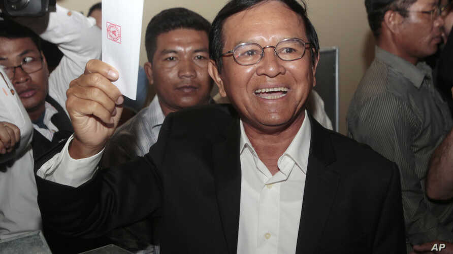 Opposition Cambodia National Rescue Party President Kem Sokha shows off his ballot before voting in local elections in Chak Angre Leu on the outskirts of Phnom Penh, Cambodia, Sunday, June 4, 2017. Cambodians are voting in local elections that could