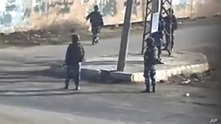 In this image taken from amateur video made available by Sham News Network in Syria  on Dec. 13, 2011, shows pro-government militia on the street in Daraa, Syria.