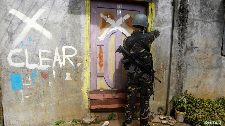 A member of the Philippine National Police (PNP) closes a door after marking a house as clear while government troops continue their assault against insurgents from the Maute group in Marawi city June 29, 2017.