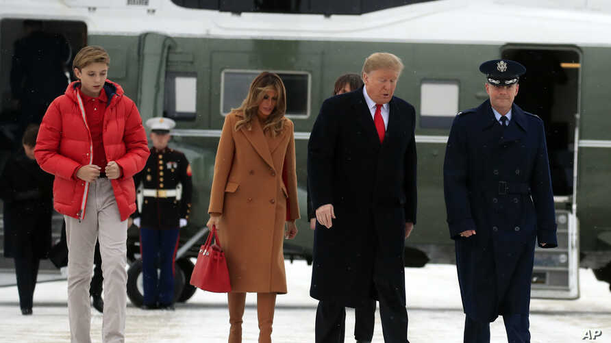 President Donald Trump walks with his wife, first lady Melania Trump, and their son Barron Trump on the tarmac of Andrews Air Force Base, Md., to switch from Marine One to Air Force One for a flight to Florida, where the first family planned to spend