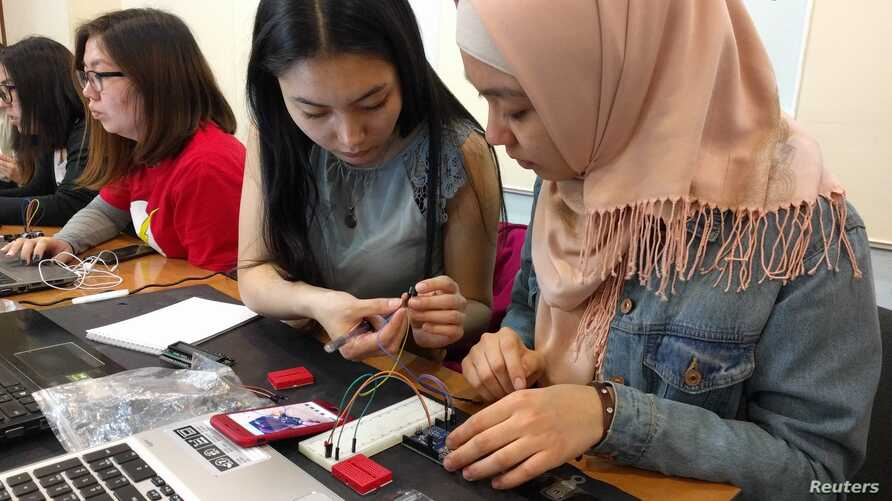Young women in Kyrgyzstan participate in a project run by Kloop Media, a local media group, to build the country's first satellite in Bishkek, Kyrgyzstan, June 4, 2018.