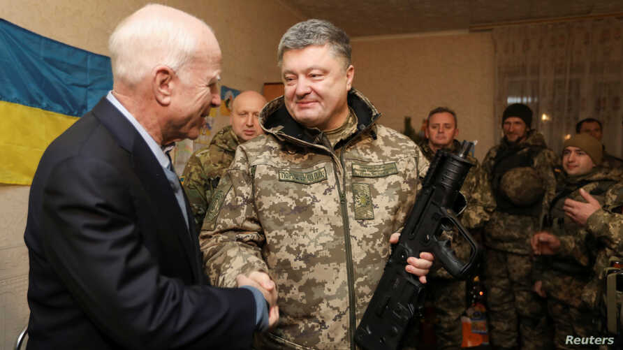 Ukrainian President Petro Poroshenko (R) shakes hands with U.S. Senator John McCain during a meeting with Ukrainian servicemen in Shirokino settlement near Mariupol, Ukraine, Dec. 31, 2016.