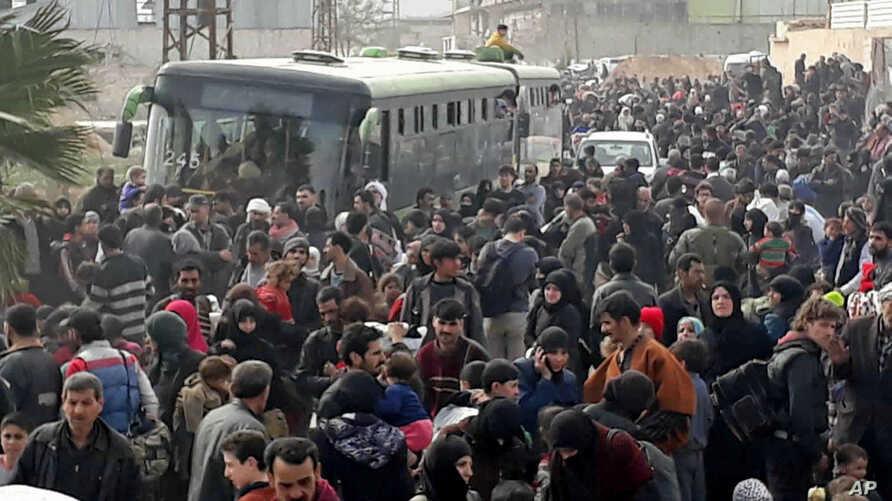 This photo released by the Syrian official news agency SANA, shows Syrian civilians with their belongings, fleeing from fighting between the Syrian government forces and rebels, in eastern Ghouta, a suburb of Damascus, Syria, March. 15, 2018.