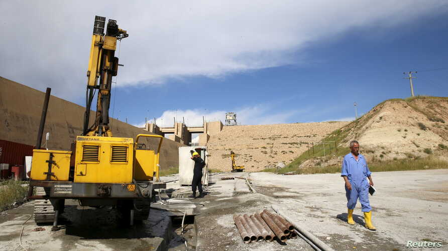 FILE - Employees work at strengthening the Mosul Dam in northern Iraq, April 18, 2016.