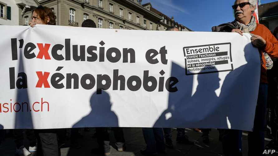 """A man holds a banner reading in French """"Together against exclusion and xenophobia, Swiss, immigrants, refugees let us unite!"""" during a demonstration in Bern against an initiative that wants to curb immigration and promote birth control in developing"""