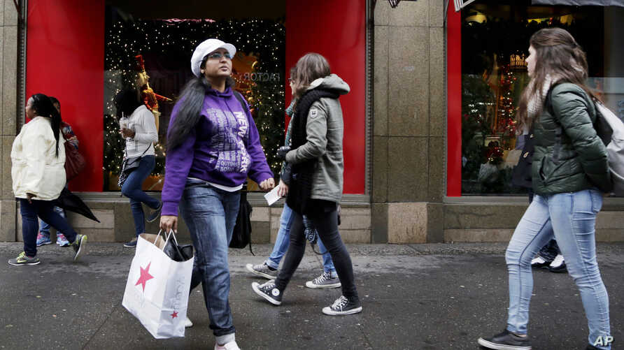 A woman walks out of a Macy's department store in Brooklyn, NY, Nov. 12, 2015.