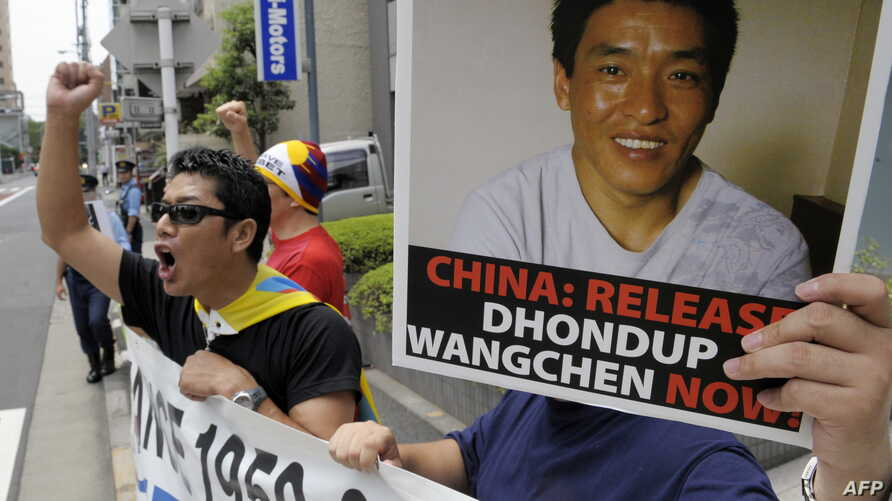 """FILE - Protesters of """"Students for a Free Tibet Japan"""" shout slogans during a demonstration to demand the release of arrested Tibetan filmmaker Dhondup Wangchen, who is pictured on the poster, in front of the Chinese Embassy in Tokyo, Aug. 1, 2009. W"""