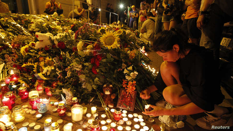 People bring flowers and candles to the Dutch embassy to commemorate the victims of the Malaysia Airlines Boeing 777 plane crash in Kyiv, July 17, 2014.